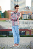 Handsome man outdoors over urban background. Full length handsome man, fashion model, with toupee posing outdoors in summertime over city background royalty free stock photography
