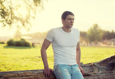 Handsome man outdoors, soft sunny sunset, man pensive Stock Image