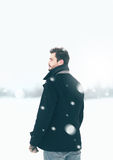 Handsome man outdoors standing in the winter blizzard. Looks into the distance stock photos