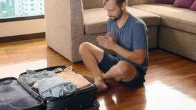 Handsome man packs a suitcase in a room with a panoramic window overlooking the skyscrapers stock photography