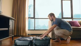 Handsome man packs a suitcase in a room with a panoramic window overlooking the skyscrapers royalty free stock photo