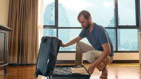 Handsome man packs a suitcase in a room with a panoramic window overlooking the skyscrapers royalty free stock image