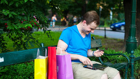 Handsome man with pad holding credit card. He is siting in park. Royalty Free Stock Photography
