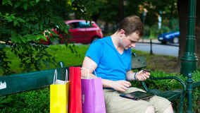 Handsome man with pad holding credit card. He is siting in park. Royalty Free Stock Images