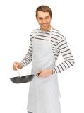 Handsome man with pan and spoon Stock Image