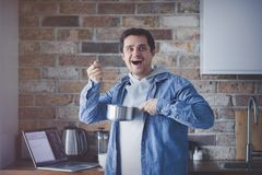 Handsome man with pan and spoon. Standing at kitchen in morning time Royalty Free Stock Photography