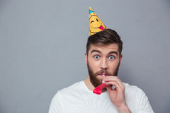 Handsome man with party hat blowing in whistle Stock Photos