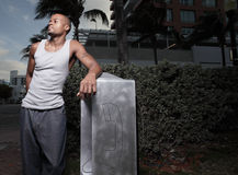 Handsome man by a payphone. Handsome African American man posing by a payphone royalty free stock photo