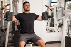 Handsome man on a pec deck machine. Young man working out at the gym on a peck deck machine Royalty Free Stock Photos