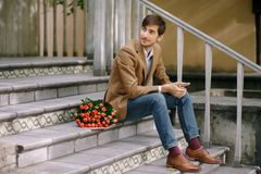Handsome man with phone and bouquet of roses. Smiling stylish man looking to right with a phone in his hands having near a bunch of roses, folded in craft paper Royalty Free Stock Image