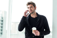 Handsome man on phone call holding disposable cup Royalty Free Stock Image
