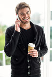 Handsome man on phone call holding disposable cup Royalty Free Stock Photos