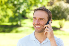 Handsome man phoning in the park Royalty Free Stock Image
