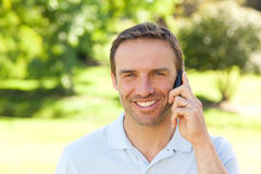 Handsome man phoning in the park Royalty Free Stock Photography
