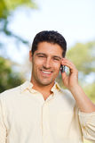 Handsome man phoning in the park Stock Images