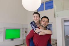 Handsome man piggybacking his girlfriend. Happy young men piggybacking his girlfriend at home Stock Images