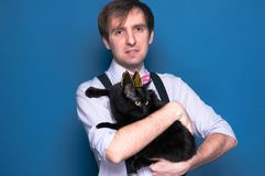man in pink shirt, bow tie and suspenders holding black cat in golden homemade crown stock image