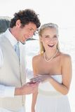 Handsome man placing ring on smiling brides finger Stock Photography