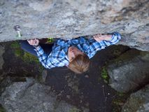 Handsome man in a plaid shirt climbs on the rock. Stock Image