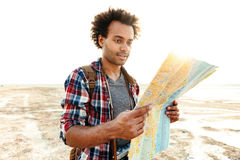 Handsome man in plaid shirt with map standing outdoors Stock Photography