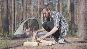 Handsome man in a plaid shirt prepares firewood to make a fire outdoors. The girl sits in a tent and plays the ukulele. Confident traveler puts firewood for the stock footage