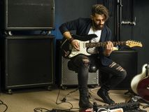 Handsome man playing an electric guitar in a studio. Photo of a man with beard sitting and playing his electric guitar in a recording studio stock photos