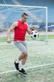 Handsome Man Playing Football in Stadium stock images