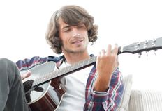 Handsome man playing on the guitar on the couch at home. Concept of lifestyle Stock Image