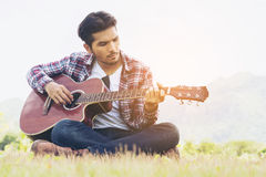 Handsome man playing guitar on green grass. Handsome man  playing guitar, sitting on green grass. Nature background. Music, guitar and nature. Country folk song Royalty Free Stock Photo