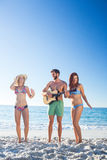 Handsome man playing guitar and his friends dancing Stock Images