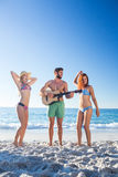 Handsome man playing guitar and his friends dancing Stock Photo