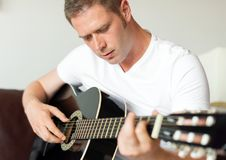 Man playing guitar. Handsome man playing guitar at home Stock Photography