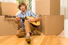 Handsome man playing guitar with moving boxes Royalty Free Stock Photos