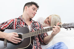 A handsome man playing guitar to a cute girl Royalty Free Stock Photos