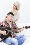 A handsome man playing guitar to a cute girl Royalty Free Stock Image