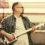 Handsome man playing his cigar box guitar Stock Photography