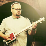 Handsome man playing his cigar box guitar Royalty Free Stock Images