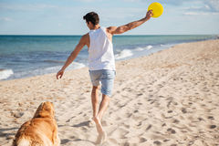 Handsome man playing with his dog on the beach Stock Photo