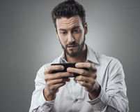 Handsome man playing with his smartphone Stock Image