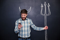 Handsome man playing role of devil standing over blackboard background Stock Images