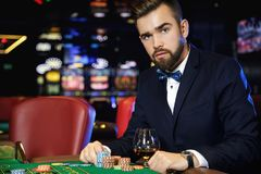 Handsome man playing roulette in the casino. Rich handsome man playing roulette in the casino royalty free stock photos