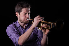 Handsome man playing on trumpet. Horizontal view of handsome man playing on trumpet Royalty Free Stock Photo