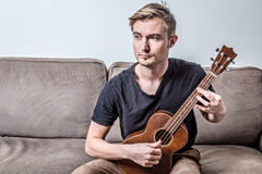 Handsome man playing ukulele or small guitar with worry feeling. On brown sofa with wahite wall in living room Royalty Free Stock Photography