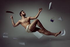 Handsome man poet levitating with his literary things. Half naked handsome man poet levitating with his literary things royalty free stock photography