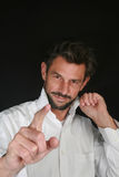 Handsome man pointing. Portrait of handsome middle aged man with beard and white shirt pointing with finger, black background Royalty Free Stock Photo