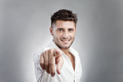 Handsome man pointing. Handsome young man in white shirt pointing, studio background Royalty Free Stock Photos