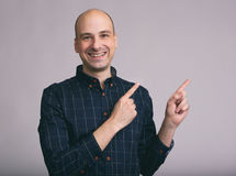 Handsome man pointing away and smiling Stock Photo