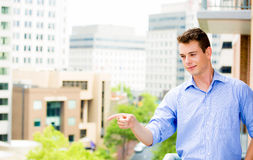 Handsome man pointing from balcony Royalty Free Stock Photos