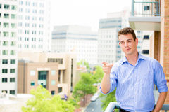 Handsome man pointing from balcony Royalty Free Stock Images
