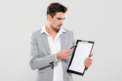 Handsome man pointing on clipboard Stock Photography